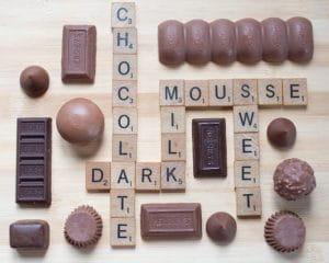 Différentes sortes de chocolats mélangées à des lettres de scrabble.